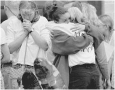 Columbine High School students in Littleton, Colorado grieving for their lost classmates. (Photo by David Zalubowski. AP/Wide World Photos. Reproduced by permission.)