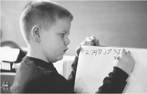 This eight-year-old boy has a learning disability that causes him to write some of these numbers backwards. Ellen B. Senisi. Photo Researchers, Inc. Reproduced by permission.)